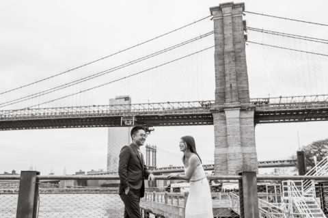 DUMBO Brooklyn NY photographing Stella and Peter's engagement. Temperature dropped dramatically, sky was covered in cloud and was windy but you can't possibly tell by Stella's chic outfit, white strap dress with white kitten heel mules and Peter in his suit and a Gucci tie. Per their outfits, my concept for Stella and Peter's engagement session geared to more editorial. As I shoot I tried to imagine a story in which I want to create and tell through my photos in every session. Stella and Peter's DUMBO Brooklyn Engagement Session captured by NY NJ Documentary Wedding Photographer Karis from Hey Karis, photographing your wedding moments cinematically.